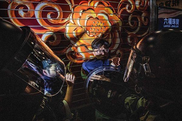2019年12月1日,香港警察在彌敦道將兩名年輕男子推到一旁並進行檢查。(NICOLAS ASFOURI/AFP via Getty Images)