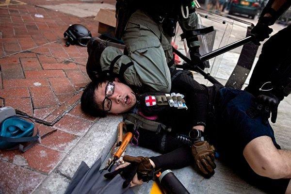 2019年10月1日,香港警察在灣仔跪壓一名年輕急救員頸部。這是2020年世界新聞攝影大賽一般新聞類故事組首獎的系列照片之一。(NICOLAS ASFOURI/AFP via Getty Images)