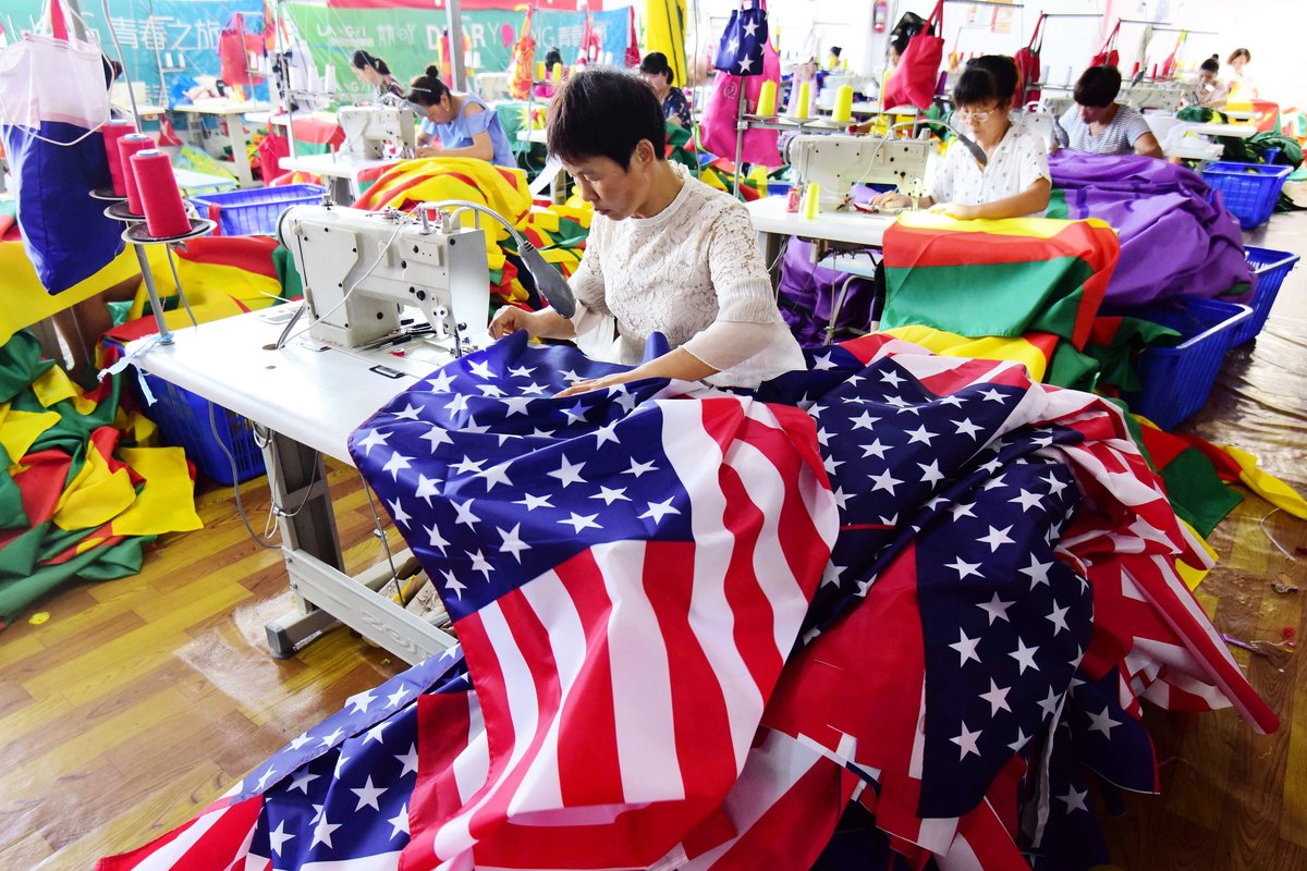 10月6日,為支持美國總統特朗普而訂購美國國旗的重慶男子黃洋,遭到當地國保傳喚和威脅。圖為正在製作各國國旗的大陸女工。(AFP)