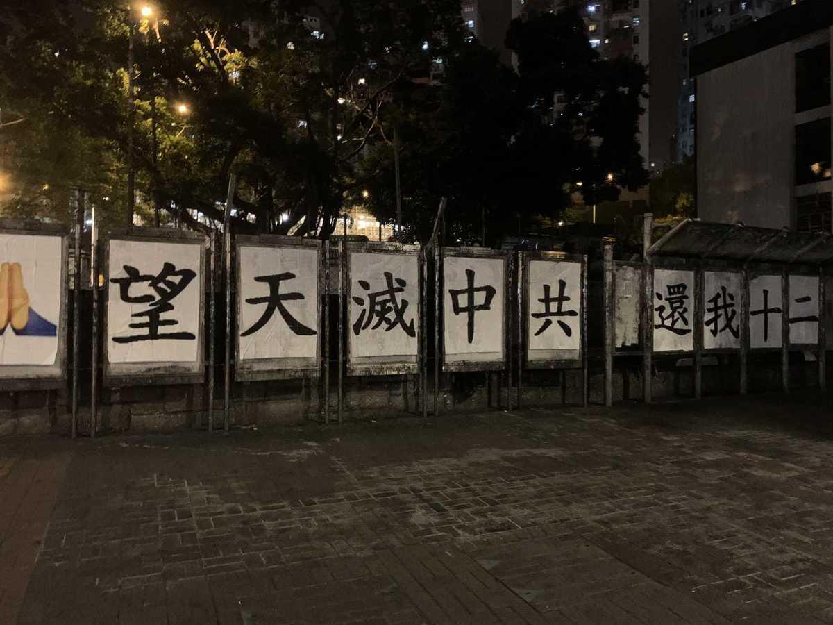 縱使熱帶風暴浪卡吹襲香港,清晨有抗爭者在觀塘連儂牆貼上「🙏望天滅中共 還我十二」的標語,期望12名遭中共羈押的港人能盡快獲釋返港。(網絡相片)