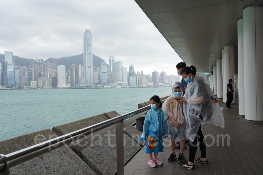 八號風球下尖沙咀碼頭仍有不少市民追風。(余鋼/大紀元)