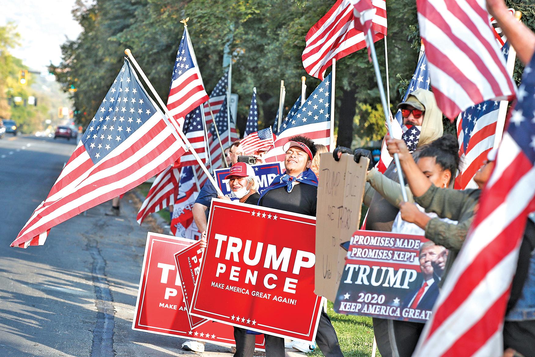 2020年10月7日,美國猶他州鹽湖城,猶他大學舉行的副總統辯論會開始之前,會場外的特朗普支持者舉著競選標語和美國國旗。(GEORGE FREY/AFP via Getty Images)