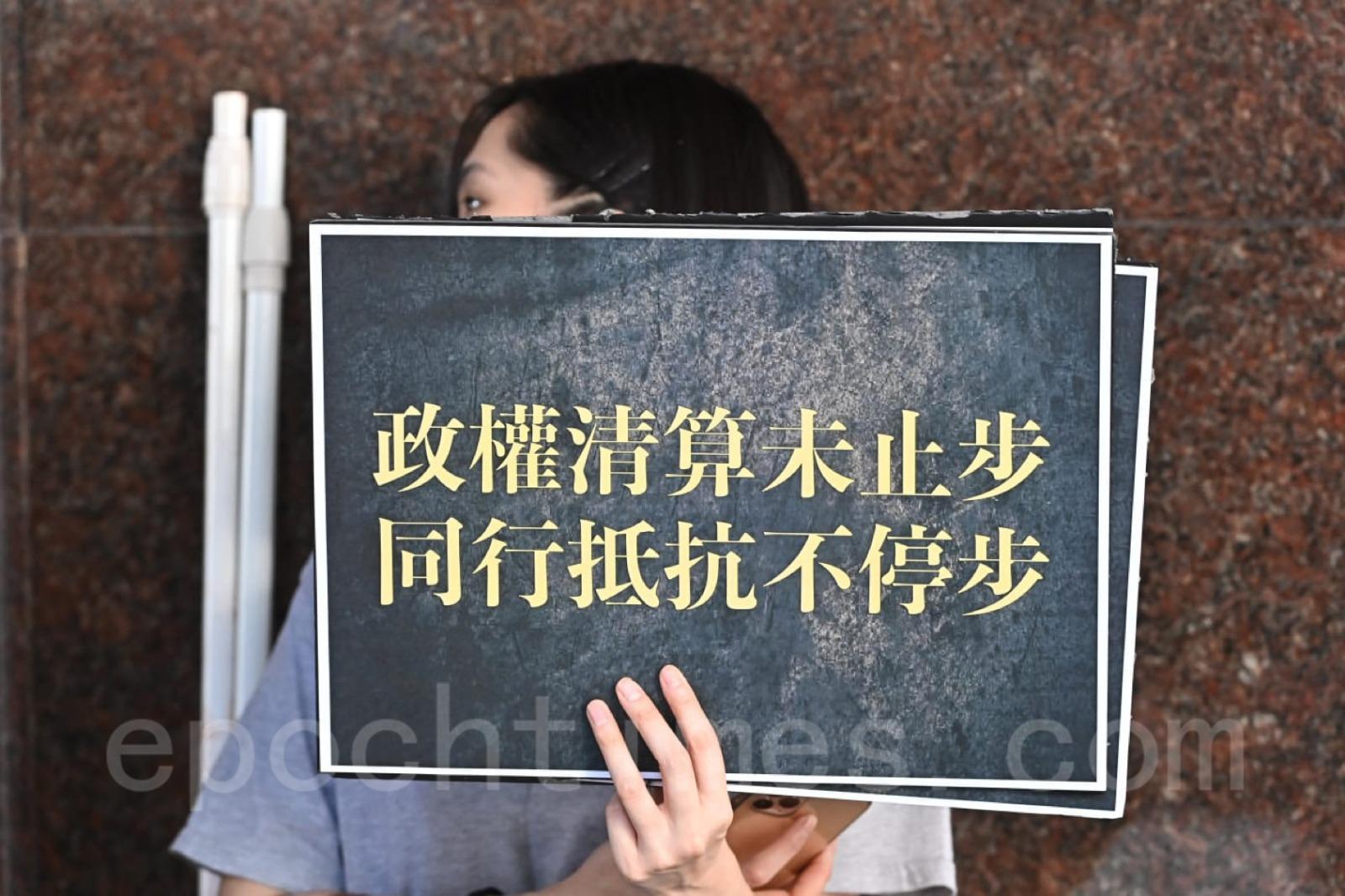 有人高舉,「政權清算未止步,同行抵抗不停步」的標語牌。(宋碧龍/大紀元)