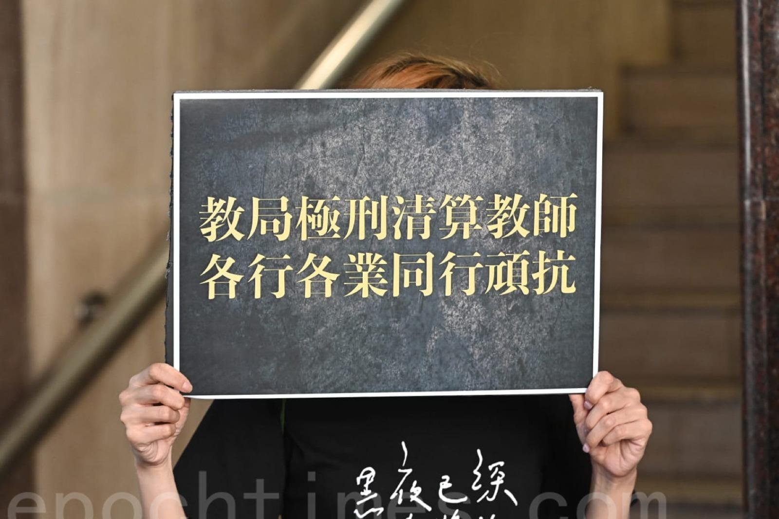 有人高舉「教局極刑清算教師 各行各業同行頑抗」的標語。(宋碧龍/大紀元)
