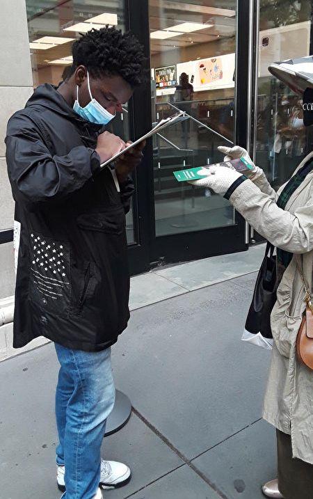 紐約非裔民眾在「打倒共產惡魔」的倡議書上簽名。(全球退黨服務中心提供)