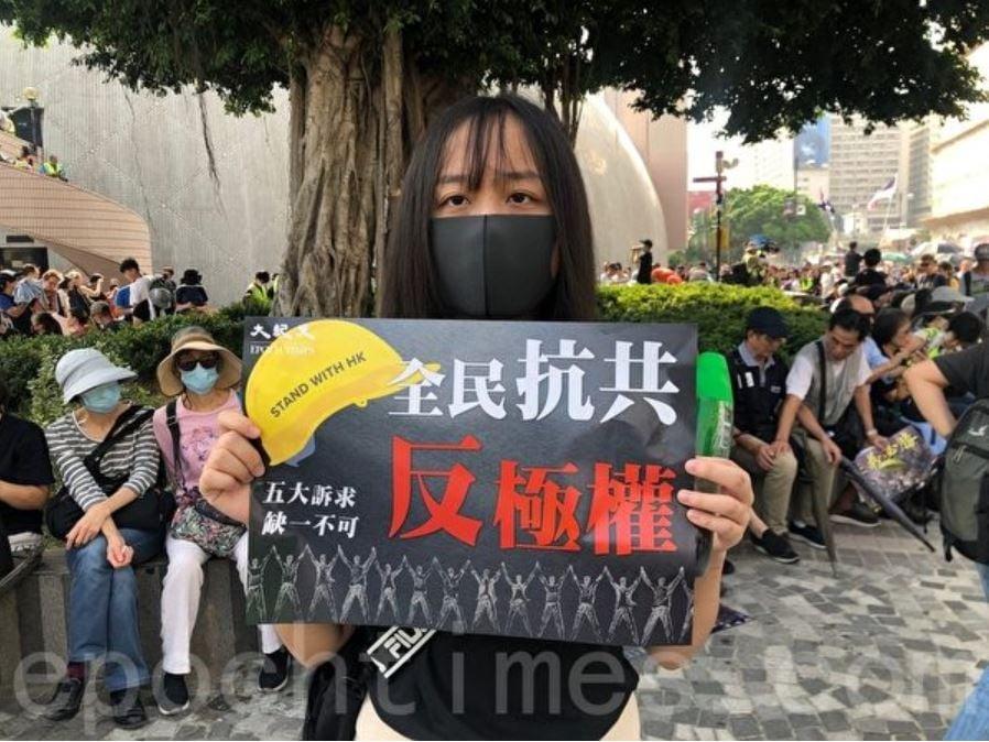 2019年10月27日,香港民眾下午三時在尖沙咀梳士巴利花園集會,追究警方使用暴力。圖為17歲中學生G同學持「全民抗共 反極權」的標語。(梁珍/大紀元)