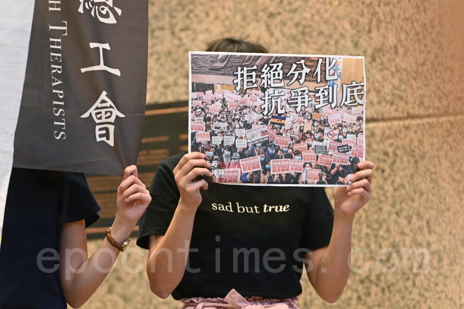 有員工手持「團結一致、對抗打壓」的標語。(宋碧龍/大紀元)