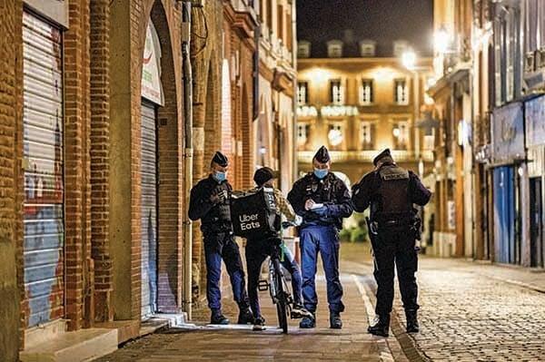 10月24日晚實施宵禁後,法國警察在南部的圖盧茲街頭盤查一名送餐員。(AFP)