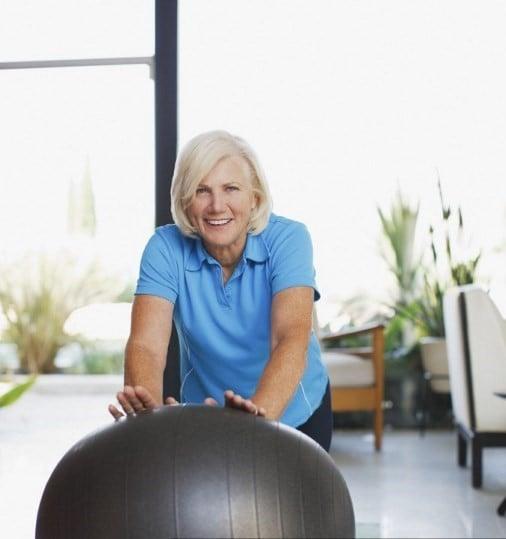 使用鍛煉球的老婦人在家。(CAIA IMAGE/通過AFP建立的科學圖片庫)