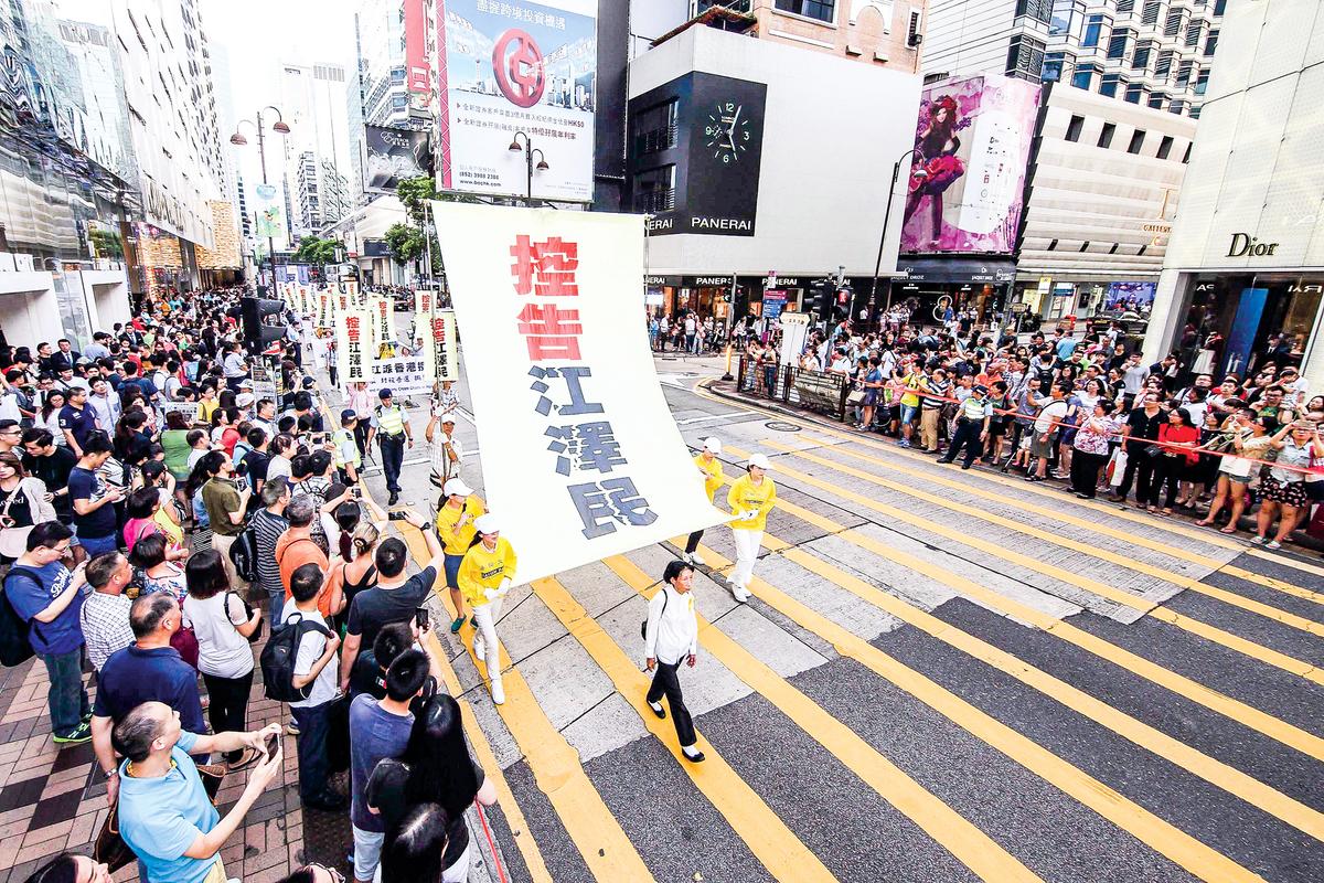 香港2015年7.1大遊行,法輪功隊伍無懼酷熱,打出訴江標語參加遊行。(大紀元)