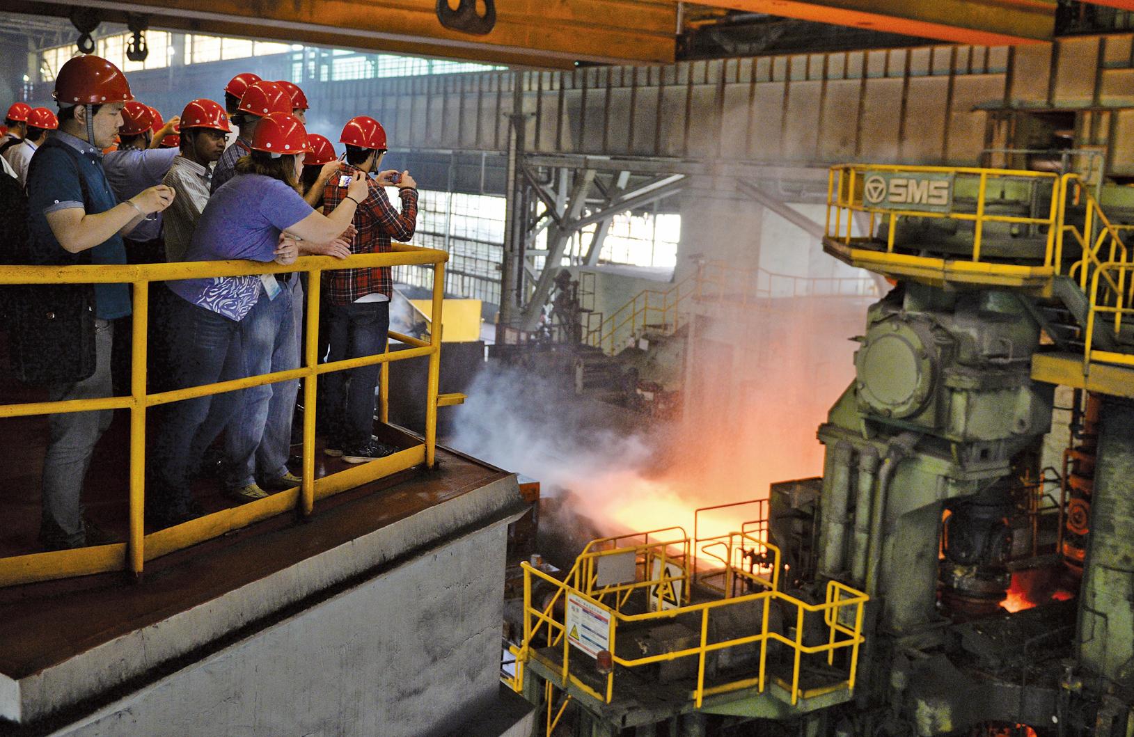 圖為2013年6月6日,在上海寶山鋼鐵廠出爐時一參觀團拍照熱軋工藝時的情景。(Getty Images)