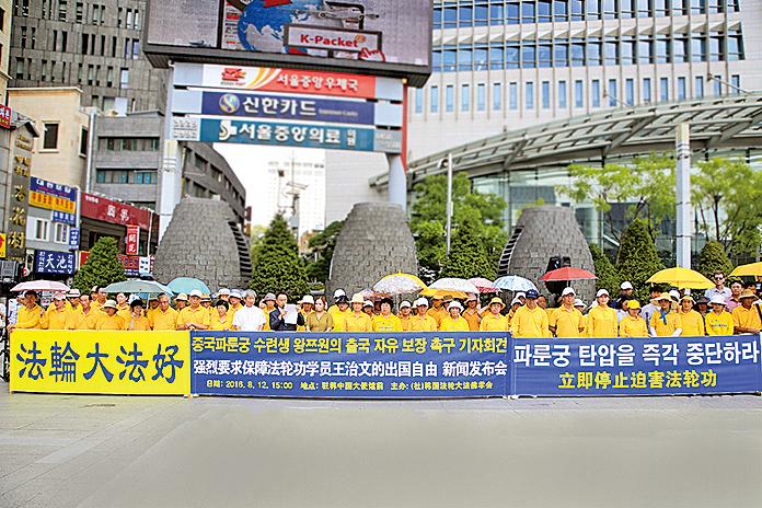 8月12日,韓國部分法輪功學員冒著酷暑在駐韓中共大使館前舉行集會,敦促中共當局重新頒發護照,還給王治文自由,使其與家人團聚。