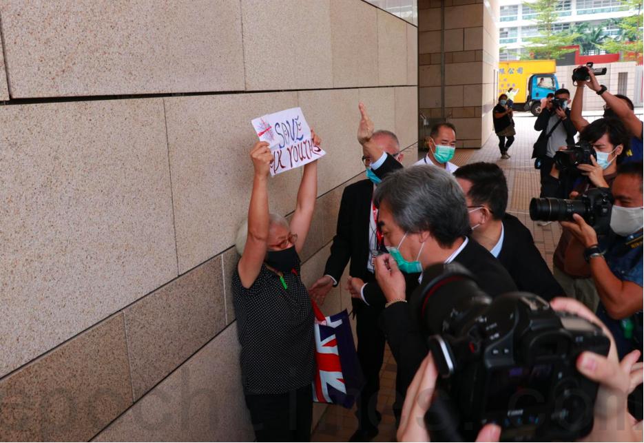 """散庭後庭外發生了一段小插曲,到庭聲援鍾翰林的王婆婆離開時舉起一張寫有 """"Save HK Youths"""" 的紙張,多名保安立即趨前並高舉雙手攔截,更加一度將王婆婆逼到牆邊,但王婆婆仍無懼色,繼續高舉紙張。(杜夫 / 大紀元)"""