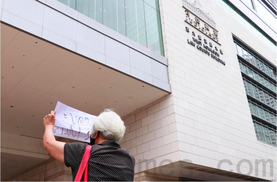 最終王婆婆在保安勸喻下到法庭門外繼續舉起紙牌,聲援鍾翰林與其他香港年輕青年。(杜夫 / 大紀元)
