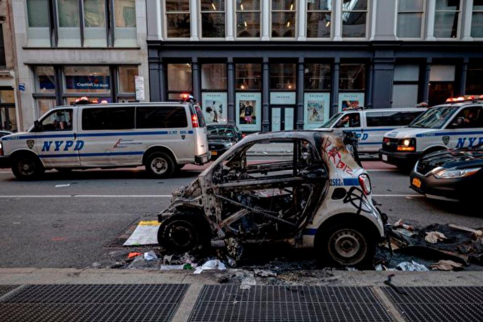圖為2020年6月1日在紐約市曼哈頓,被安提法暴徒燒燬的警車。街道兩邊的商店也遭到打砸搶。(JOHANNES EISELE/AFP via Getty Images)