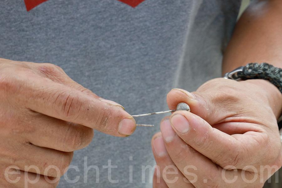 用萬字夾(其它幼細針狀物)貫穿草珠子。(曾蓮/大紀元)