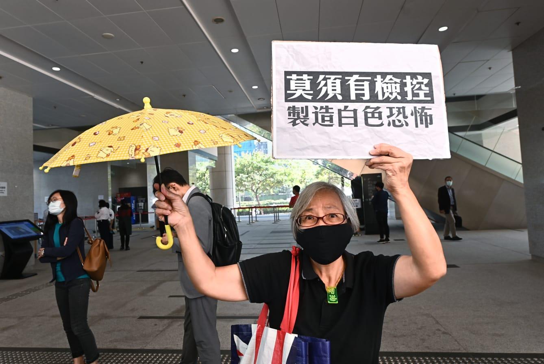 11月6日下午,聲援民眾在西九龍裁判法院,舉牌抗議當局政治打壓。(宋碧龍/大紀元)