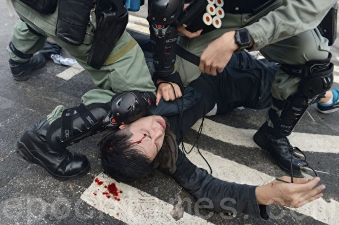 2019年11月12日,在香港中大校園裏,學生被警察摁在地上毆打,致頭破流血。(宋碧龍/大紀元)