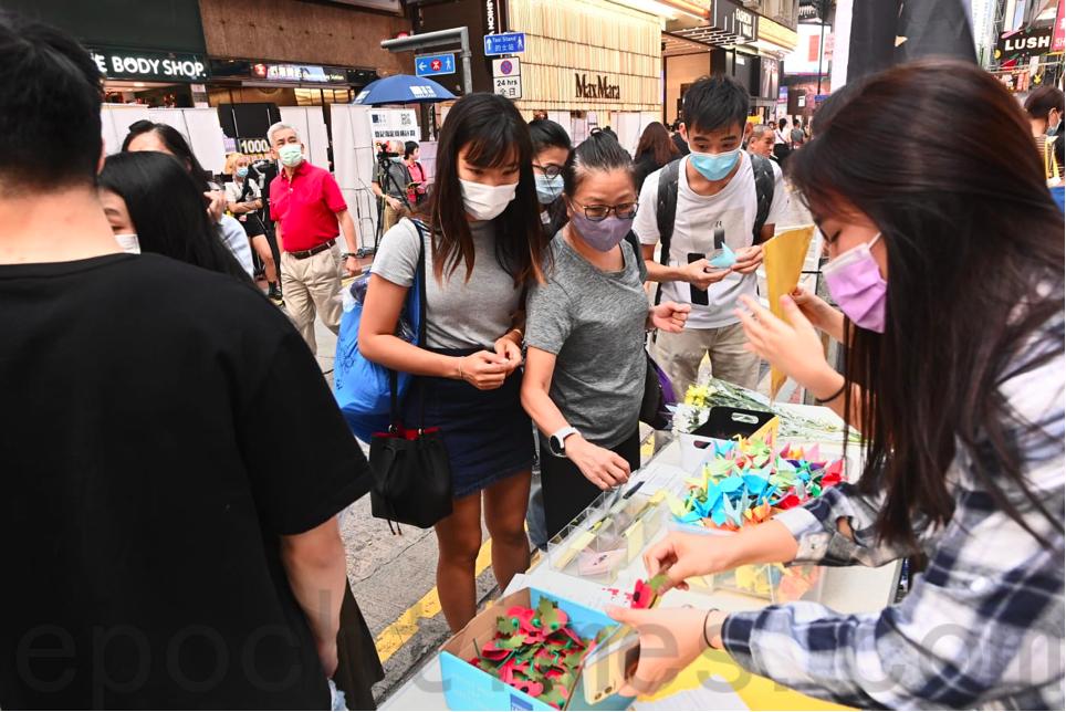 賢學思政在銅鑼灣擺設街站向市民提供彩色紙,很多市民折紙鶴寄託哀思。(宋碧龍/大紀元)