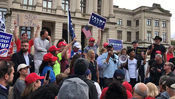 民主黨籍議員弗農˙瓊斯(Vernon Jones,持擴音喇叭者)及共和黨新人瑪喬麗‧泰勒‧格林(Marjorie Taylor Greene立於瓊斯左方金髮女士)到場聲援。(呂尚明/大紀元)