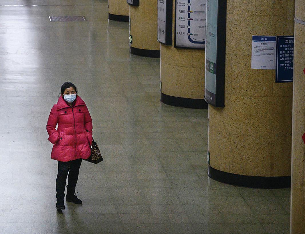 中共肺炎導致大陸經濟大幅下滑。圖為2020年2月3日,一名戴著口罩的女士站在北京一處空蕩蕩的地鐵月台上。(Kevin Frayer/Getty Images)