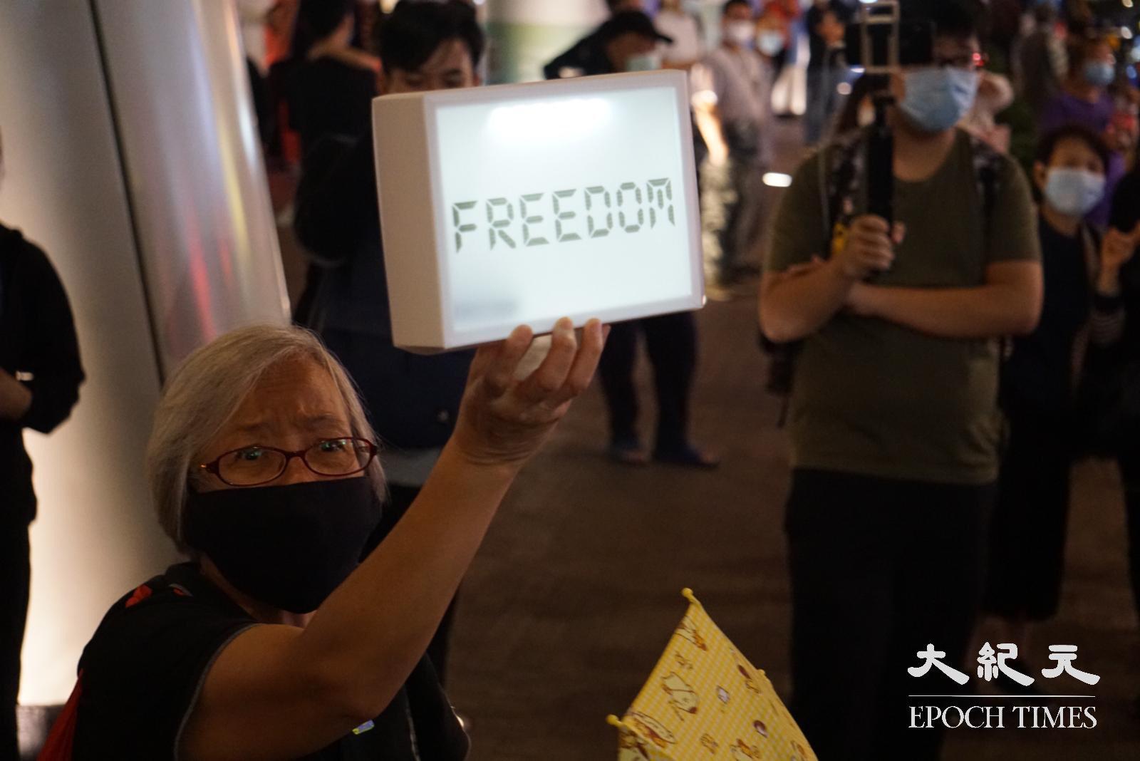 王婆婆高舉寫有「 Freedom」(自由)的標語。(Jerry/大紀元)