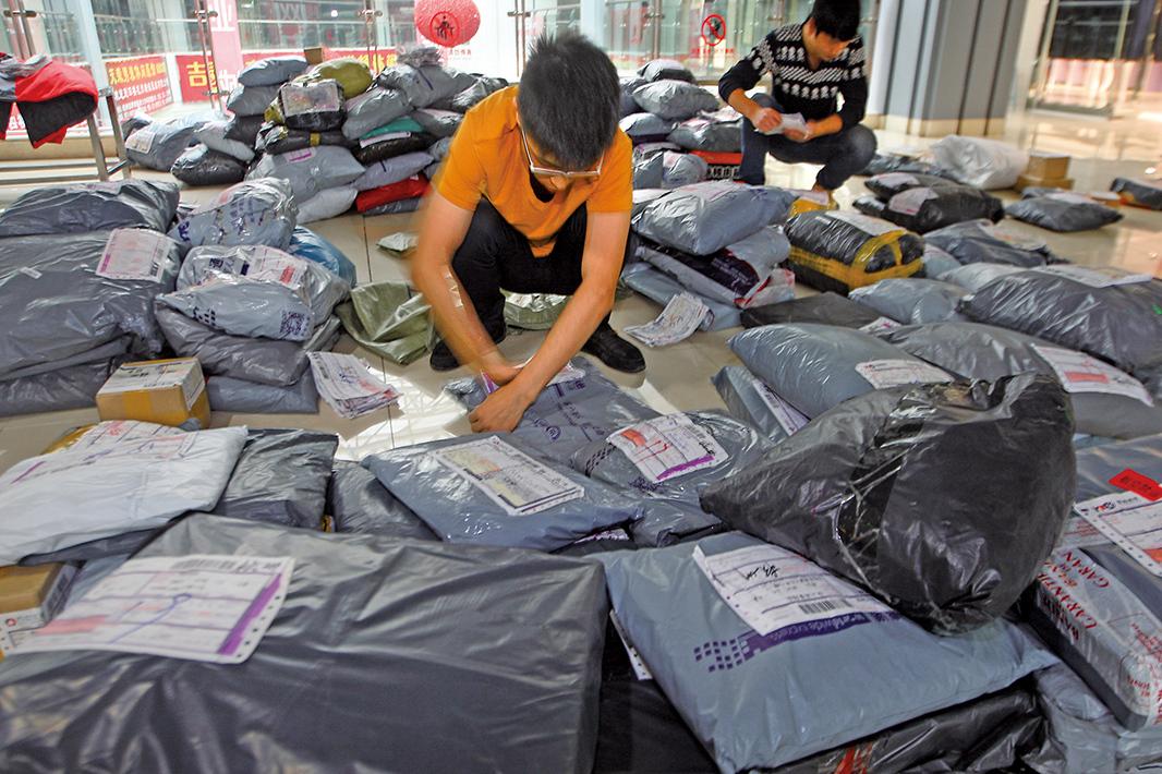許多消費者在「雙十一」衝動購物之後反悔,選擇退貨。圖為2015年11月19日,浙江省杭州市,正在低頭處理退件的快遞員。(大紀元資料室)