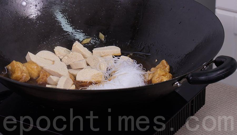 將粉絲、素雞加入蠔油汁中,翻炒均勻。(陳仲明/大紀元)