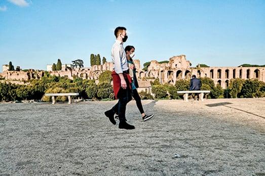 11月11日,意大利第二次實施嚴格防疫封鎖措施後,戴著口罩的行人沿著古羅馬馬戲團古老的羅馬戰車賽場散步。(AFP)