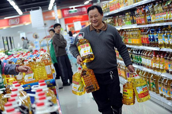 近幾個月來,原材料價格暴漲,引發大陸物價連鎖性不斷上漲,漲價商品範圍涉及百姓生活方方面面。圖為:11 月2 日,浙江嘉興一超市內,一市民一次性購買6 桶食用油。(大紀元資料室)