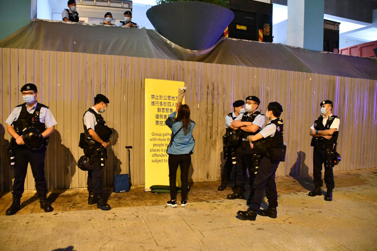 街坊黃小姐被在場警方阻止獻花,只好無奈地在花壇四方拜祭。( Big Mack/大紀元)