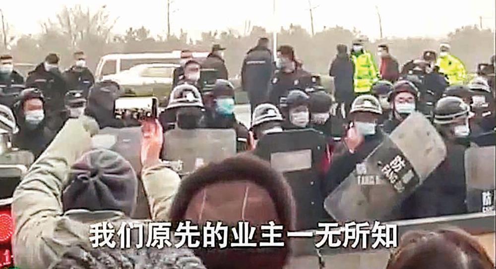 北京市昌平九華別墅區業主與被路障擋住的帶防暴盾牌的黑衣人對峙,並對其喊話說,業主對當局的強拆事先一無所知。(影片截圖)