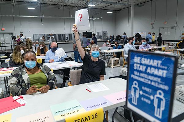 2020年11月13日,在佐治亞州勞倫斯維爾開始重新點票時,格溫內特縣的一名工人舉了一張紙,表明她有一個問題。(Megan Varner/Getty Images)