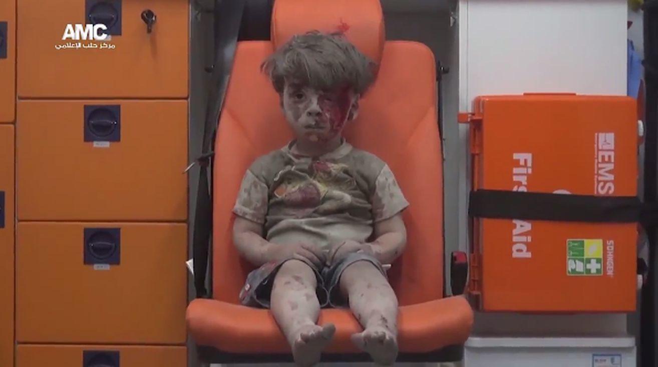 一名敘利亞小男童在瓦礫堆中被救出來,不但全身沾滿灰塵,半邊的臉龐全是紅色的血跡,令人看了痛心不已。(視像擷圖)
