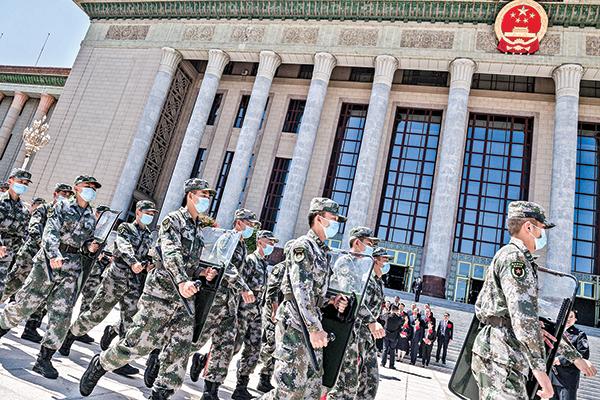 近日,習近平主持召開中共政治局會議,高調要求「聚焦備戰打仗」。圖為 9 月一隊軍人從人民大會堂前走過。(Getty Images)