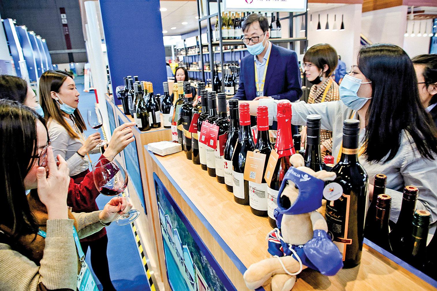 近日,中共商務部宣佈,對澳洲葡萄酒最高加徵212%的反傾銷稅。圖為11月在上海舉行的國際進口博覽會上,人們在品嚐來自澳洲的紅酒。(Getty Images)