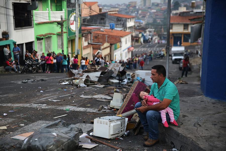 世界上沒有哪個國家像委內瑞拉曾經這樣富有、而潰敗起來又是如此迅猛。圖為一位父親和女兒坐在委內瑞拉一個城市破敗的街頭,而背景是購買必需品的長隊。(John Moore/Getty Images)