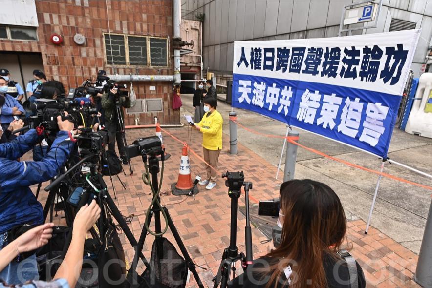 法輪功學員代表在寫有「人權日跨國聲援法輪功」、「天滅中共 結束迫害」的橫幅前發言,有眾多媒體到場。(宋碧龍/大紀元)