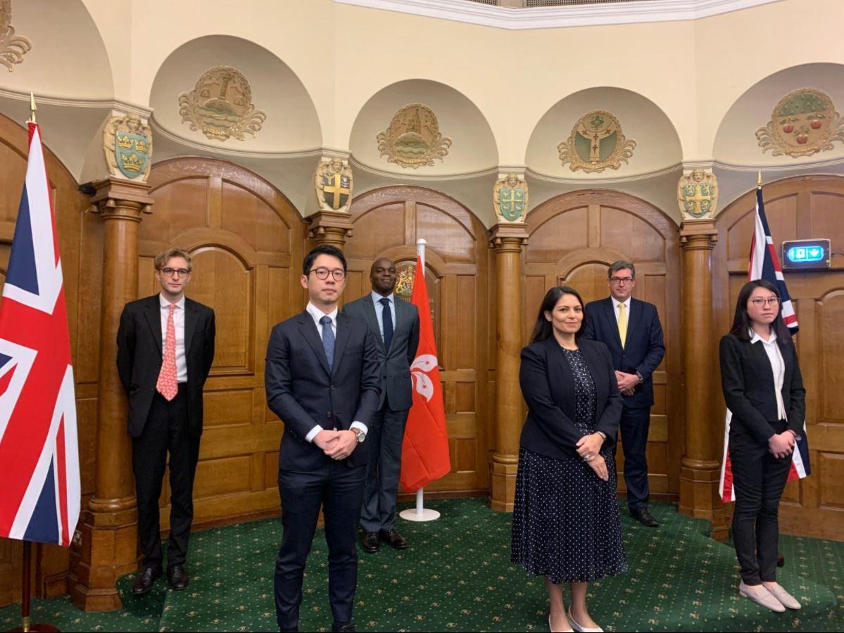 2020年12月9日,英國內政大臣彭黛玲(前排中)會晤羅冠聰(前排左)和12港人家屬Beatrice Li(前排右)等人,他們的身後懸掛著英國國旗和香港特區區旗。(羅冠聰臉書截圖)