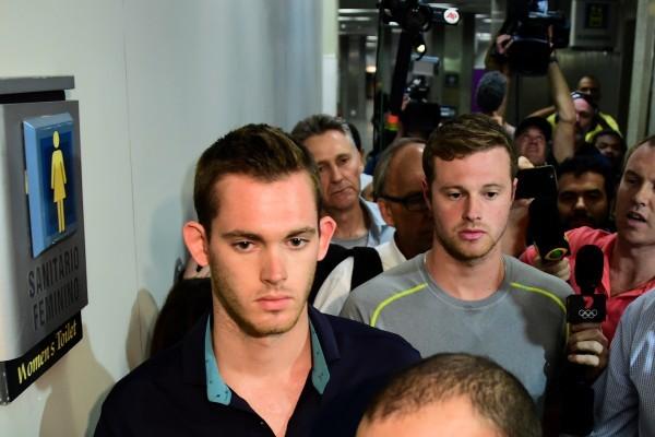 之前遭巴西警方巴西警方扣留禁止離境的美國游泳選手岡納・本茨(Gunnar Bentz,左)和傑克・康格(Jack Conger,中)18日晚已獲准離開巴西回美國。圖為他們走出里約警察局。(TASSO MARCELO/AFP/Getty Images)