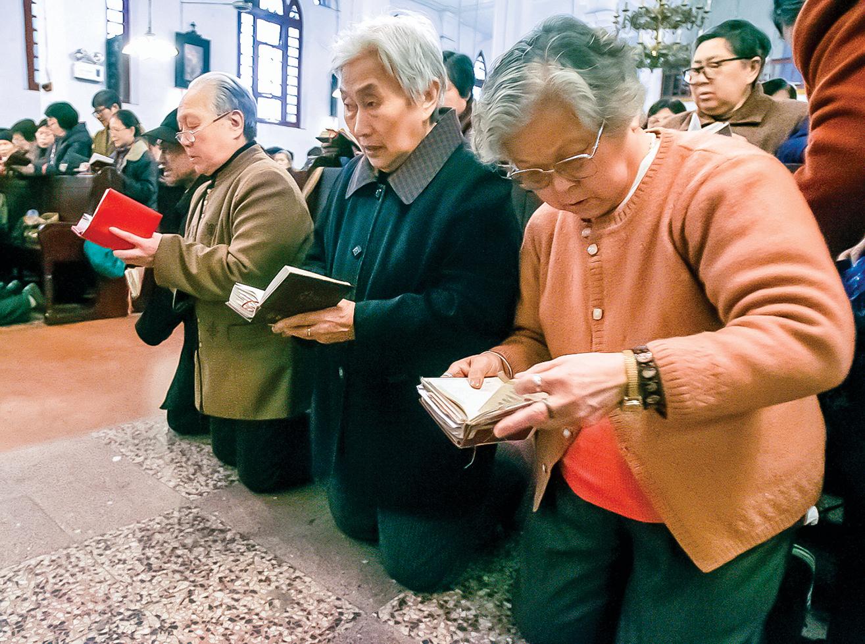 2007年,在重慶市的教堂裏,老年信徒跪著讀聖經、祈禱。(Getty Images)
