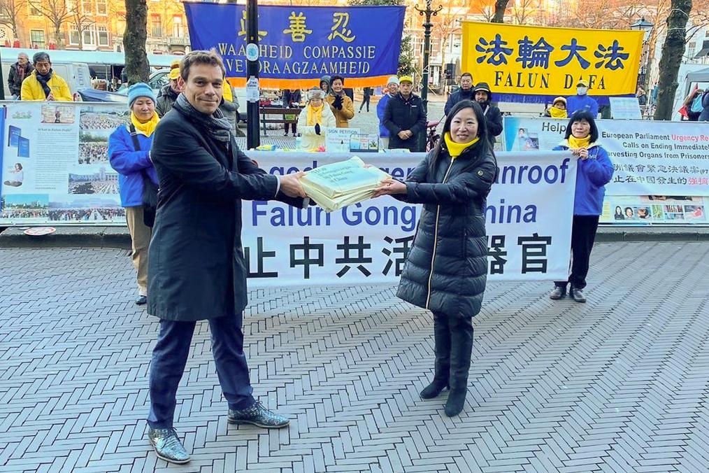 荷蘭議員赫爾維特先生(Martijn van Helvert,左)正式接收荷蘭法輪大法學會發起的《制止活摘器官、制止迫害法輪功學員徵簽表》。(Vincent Zhao/大紀元)