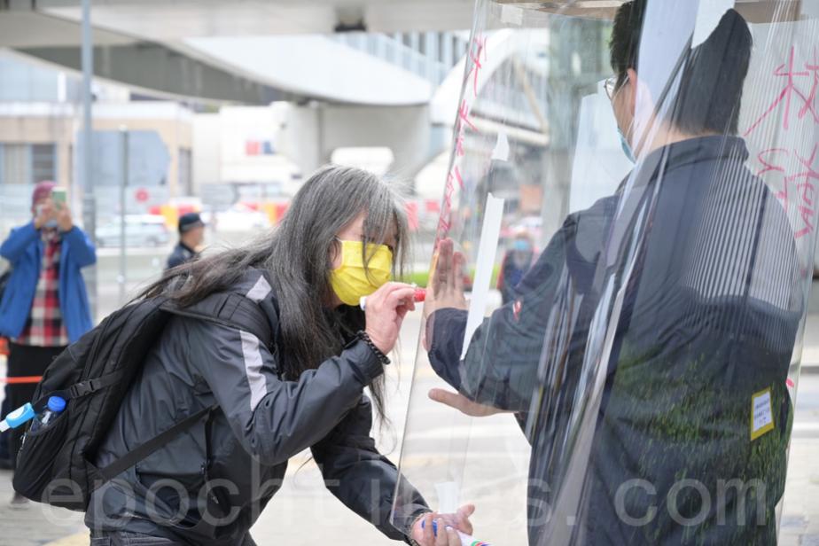 社民連梁國雄(左)在膠筒上寫下「失業貧窮當透明」。(Bill/大紀元)