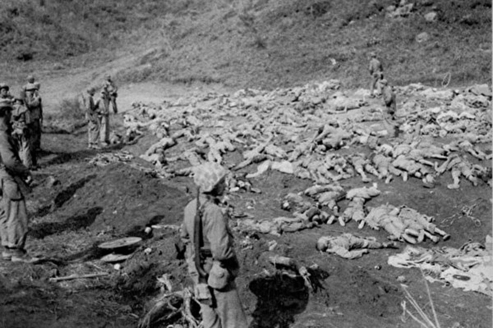 美軍士兵正在檢視韓戰中陣亡的中國士兵屍體。(公共領域)。