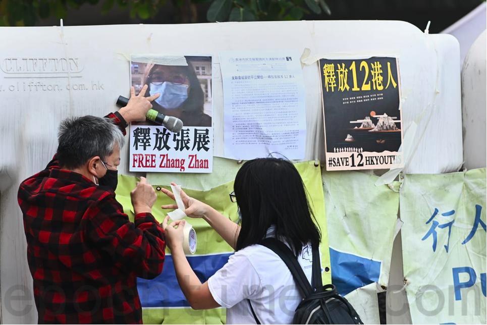 支聯會12月28日遊行到中聯辦抗議,成員將寫著「釋放張展」、「釋放12港人」字樣的標語貼在水馬上。(宋碧龍/大紀元)
