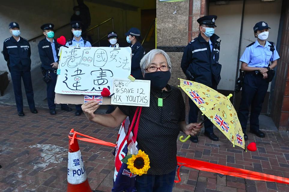 2020年12月28日12港人被審,王婆婆在中聯辦前高舉黃傘與「港區國安法違憲」標語。(宋碧龍/大紀元)