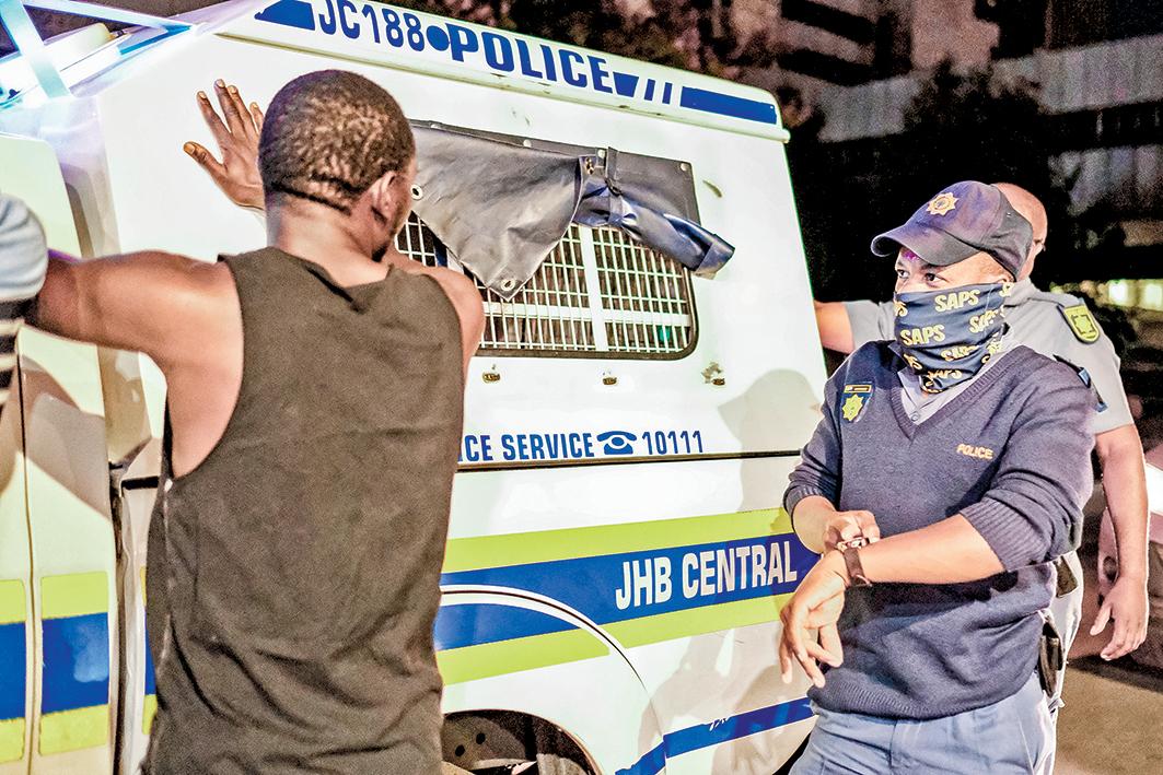 12月29日,南非實行三級防疫限制措施後,一名警察(右)向行人詢問,為何過了宵禁時間仍不回家。(AFP)