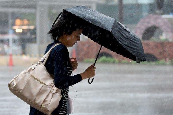 8月22日,颱風「蒲公英」登陸日本關東地區,中午左右,颱風「蒲公英」進入伊豆半島和千葉縣南部。圖為颱風經過東京都內時街上行人。(Getty Images)