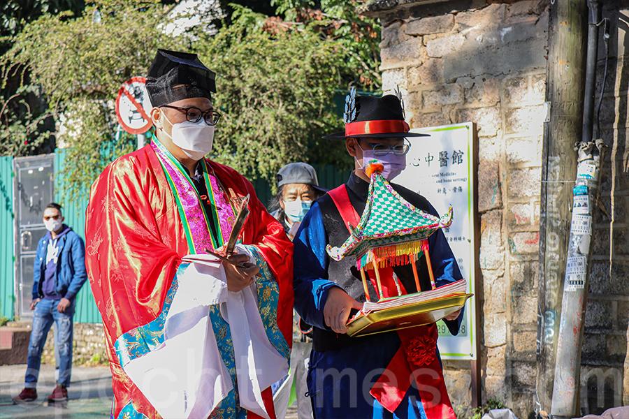 彭建臻(右)是頭名緣首,負責全程捧著「意亭」,上面擺放著寫有村民姓名的「意文」,他還需要袋著一把「關刀」,以保護重要的「意文」。(曾蓮/大紀元)