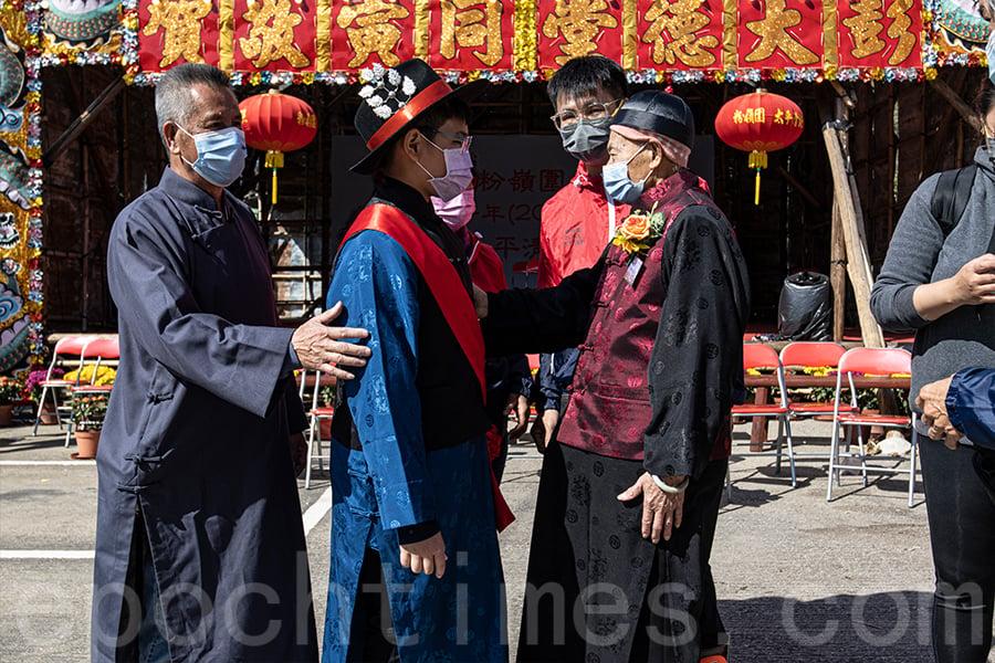 年逾九旬的族長彭焯明(右),在連日打醮的結束之際,勉勵12歲的頭名緣首彭建臻(中)。(陳仲明/大紀元)